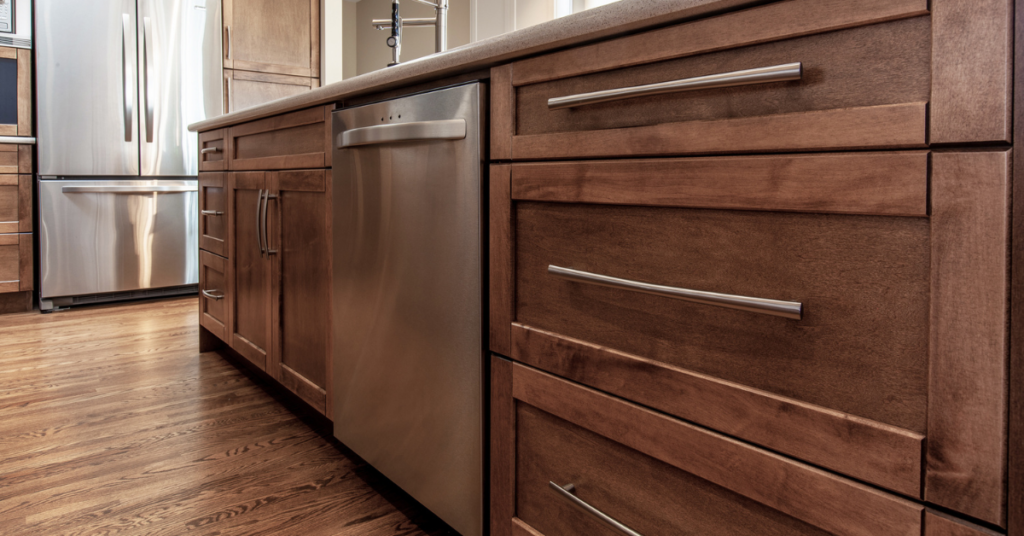 Long brushed nickel handles/pulls on warm stained shaker maple cabinets.