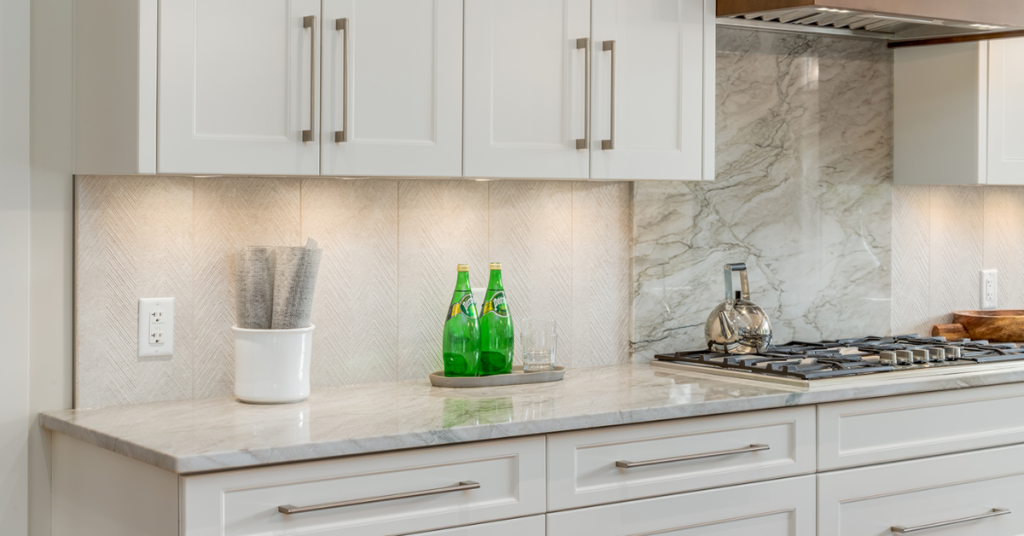 Modern transitional handles in brushed nickel finish on white shaker cabinets.