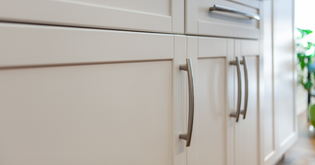 Open end handles in a brushed nickel finish on white shaker cabinets.