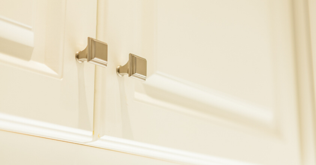 White raised panel cabinets with square knobs in a brushed nickel finish.