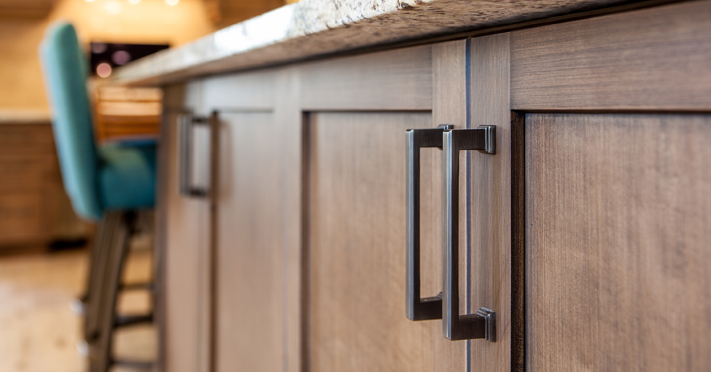 Modern square matte black handles on chocolate brown wood finished cabinets.