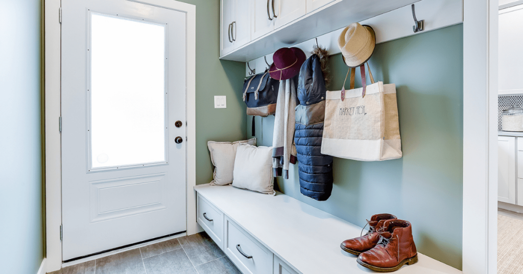 Custom mudroom with a teal wall, white cabinets, coats, hats and bags hanging on hooks, cabinet design by Superior Cabinets.