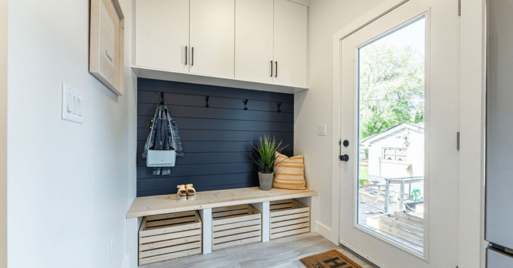 Custom mudroom with white wall cabinets, open wood basked below, navy blue shiplap wall, cabinets by Superior Cabinets.
