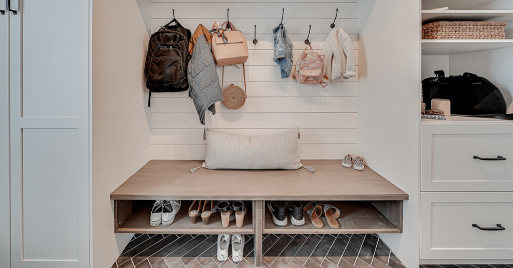 Custom mudroom with white and brown cabinets, ample shoe storage, design by Superior Cabinets.