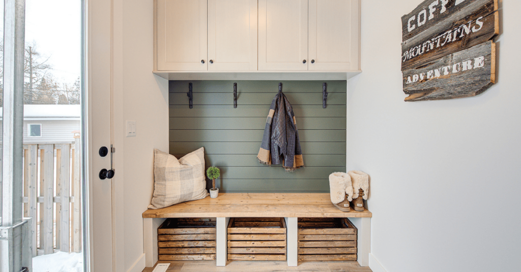 Custom mudroom with white wall cabinets, open wood basked below, cabinets by Superior Cabinets.