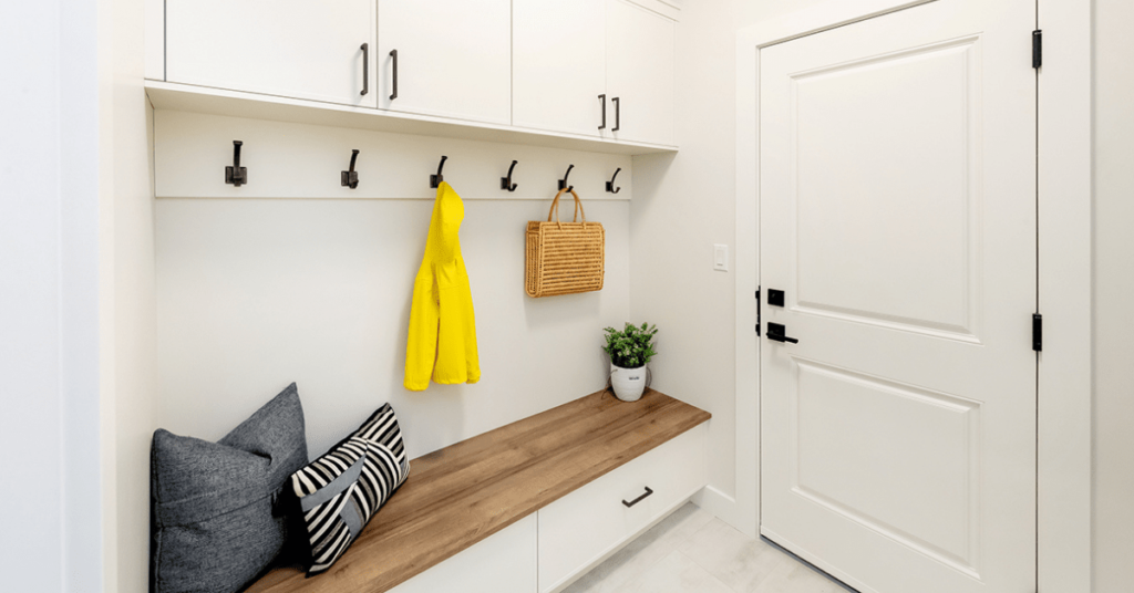 Custom mudroom with white cabinets, black wall hooks, warm wood bench seat, cabinets by Superior Cabinets.
